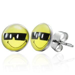 Stalowe kolczyki, przyjacielski uśmiech w czarnych okularach, wkręty